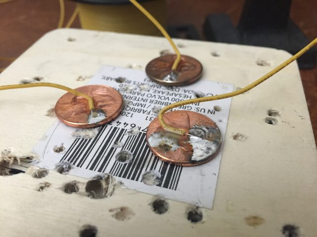 I put pennies on wood to help them get hot as I solder to them.